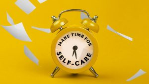 """Alarm clock with the numbers replaced to read """"Make time for self-care"""", loose sheets of paper fall behind it"""