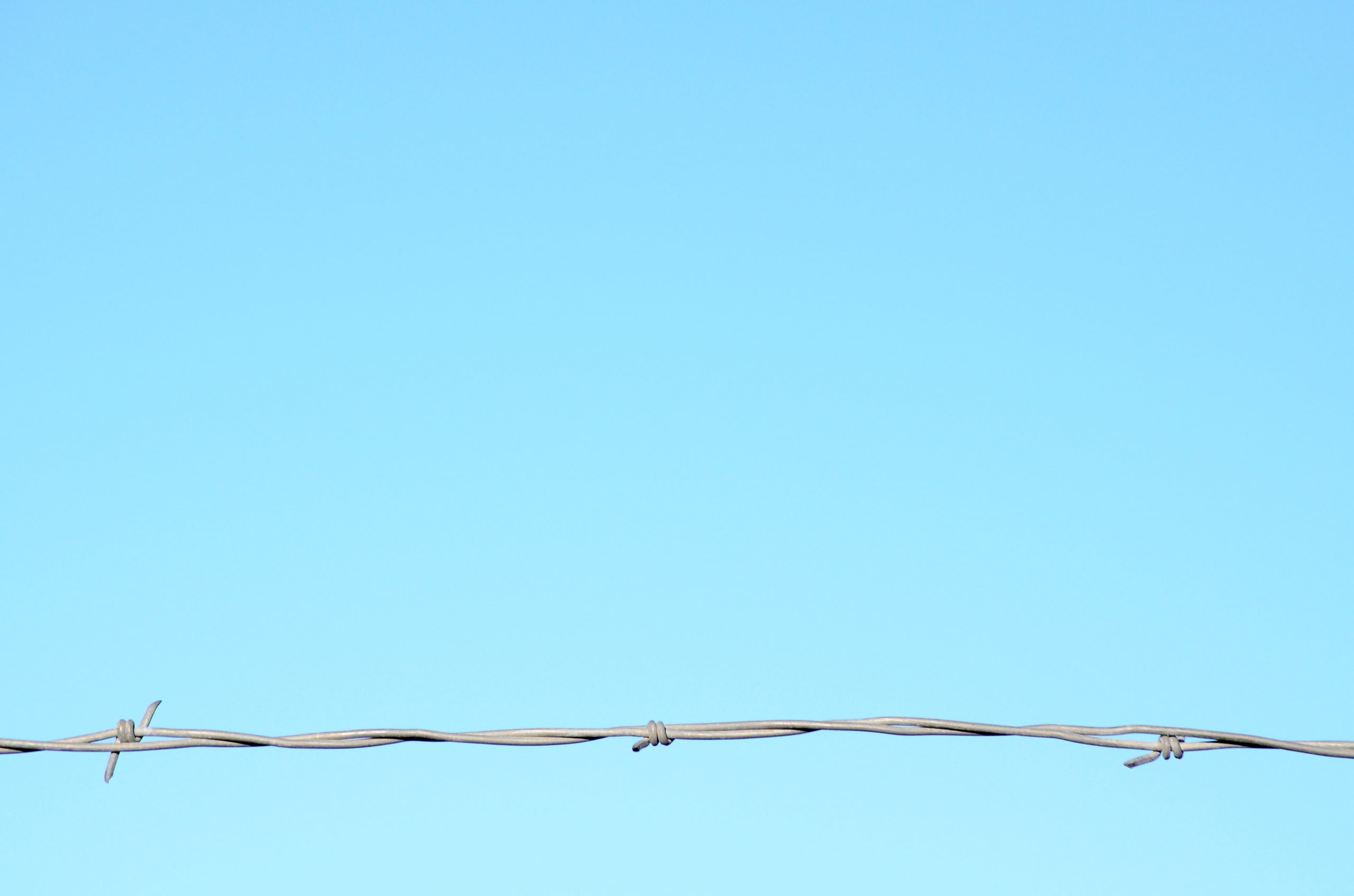 Close-up of razor wire against a clear blue sky